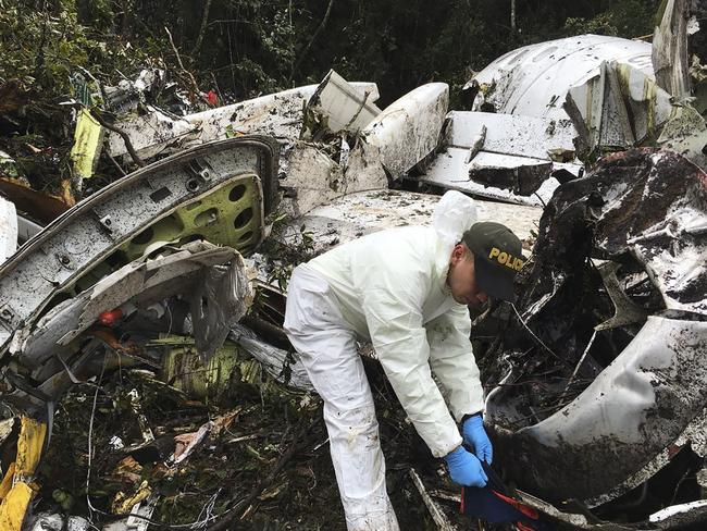 A police officer sifts through the wreckage of the chartered aeroplane that crashed in La Union, outside Medellin, on November 28 local time. Picture: Colombia National Police via AP