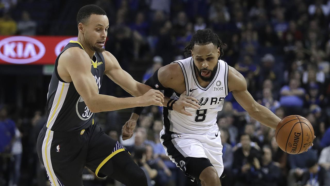 San Antonio Spurs' Patty Mills (8) drives the ball against Golden State Warriors' Stephen Curry.