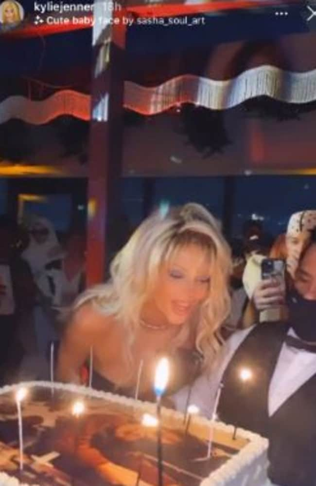 Kendall blew out her candles as a worker, who was masked, held the cake