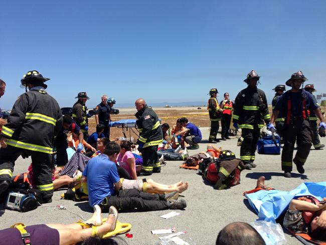 Passengers from Asiana Airlines flight 214 are treated by first responders on the tarmac.