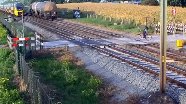 The cyclist can be seen waiting for the freight train to pass. Picture: ProRail/Youtube