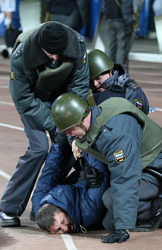 Police detain a fan during the incident. Picture: AP Photo/Alexander Mysyakin