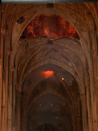 Shocking photos from inside the cathedral show the smouldering roof. Picture: Philippe Wojazer