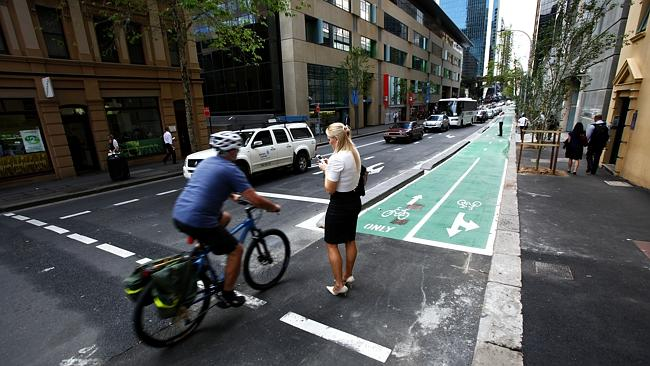 Woman distracted by her phone wanders onto the road and has a near miss with a cyclist in Sydney.