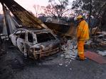 CFS firefighter looks over a burnt out car and building on Devils Gully Rd, Kersbrook. Picture: Campbell Brodie.