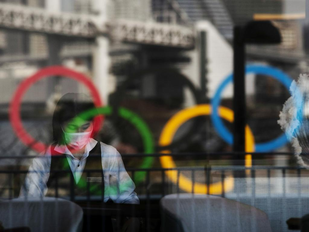 The Olympics rings are reflected on the window of a hotel restaurant as a server with a mask sets up a table Monday, Feb. 24, 2020, in the Odaiba section of Tokyo. (AP Photo/Jae C. Hong)