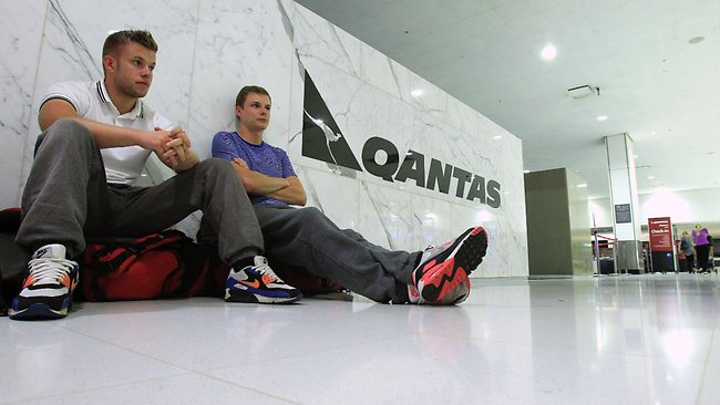Kevin and Chris Crulley sit on the floor at the Qantas check-in counter at Sydney Airport in Sydney. Picture: Rick Rycroft / AP