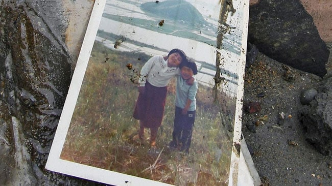 A family picture lies among the rubble in Higashimatsushima, Miyagi Prefecture, northern Japan, Monday, March 14, 2011, three days after a massive earthquake and the ensuing tsunami hit Japan's east coast. (AP Photo/Kyodo News) JAPAN OUT, MANDATORY CREDIT, NO SALES IN CHINA, HONG KONG, JAPAN, SOUTH KOREA AND FRANCE