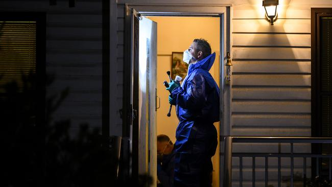 Police examine the Sutherland home where the bodies of David Reid's parents were found.