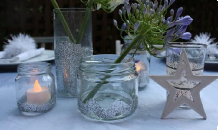 <strong>JAZZ UP YOUR CANDLES:</strong> No need to buy expensive candles to create a festive glow to the Christmas table. Use any bottle or clean jar, add a tea-light and get creative with glitter and greenery.