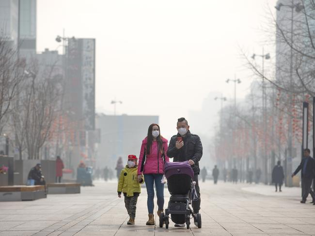 A family visit a normally crowded shopping street in China's capital. Picture: AP Photo/Mark Schiefelbein.