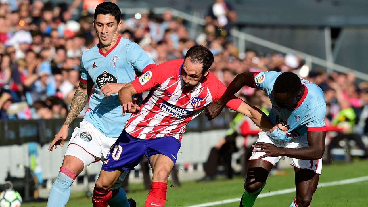 Atletico Madrid's Uruguayan defender Diego Godin (C) vies with Celta Vigo's Danish midfielder Pione Sisto (R)
