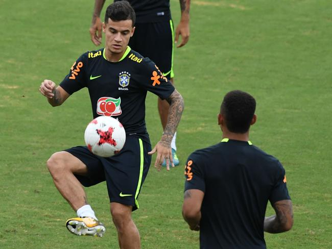 Brazil's Coutinho (L) takes part in a training session.