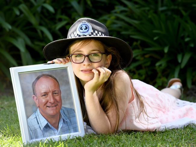 Darcy Thomas, 8, with a photo of her dad Detective Sgt David Thomas, who died suddenly at home in front of his family of a heart attack. Picture: Tricia Watkinson