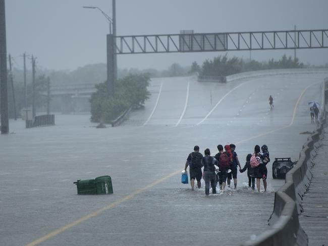 Evacuation residents from the Meyerland area walk onto an I-610 overpass for further help during the aftermath of Hurricane Harvey. Picture: Brendan Smialowski/AFP