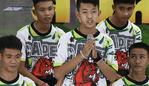 Pornchai Khamluang (C), one of the twelve boys dramatically rescued from deep inside a Thai cave after being trapped for more than a fortnight, speaks during a press conference in Chiang Rai on July 18, 2018, following their discharge from the hospital while coach Ekkapol Chantawong (front-L) and Adul Sam-on (front-R) looks on. The young footballers and their coach who became trapped deep in a flooded cave complex tried to dig their way out and survived on rainwater for nine days before being found and later rescued. / AFP PHOTO / Lillian SUWANRUMPHA