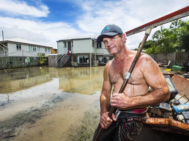Railway Estate resident Johnny Brock attempting to clean up his flood ridden property which proved troublesome as flood waters again rose on Wednesday. Picture: Lachie Millard