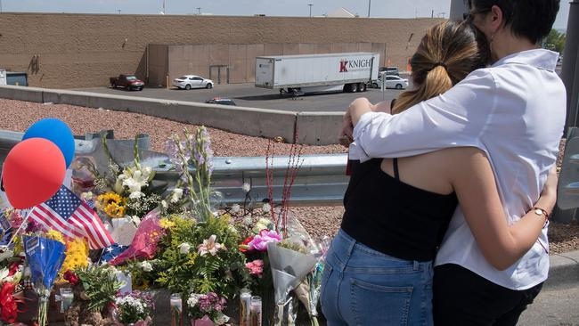 People hug beside a makeshift memorial outside the Cielo Vista Mall Walmart. Picture: Mark Ralston/AFP