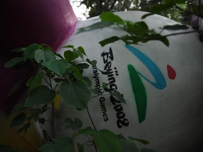 This photo taken in July this year shows Fu Niu Lele, the mascot for the 2008 Beijing Paralympic Games, lying among trees behind an abandoned, never-completed mall in Beijing. Picture: Greg Baker