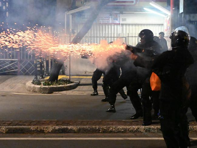 Indonesian police officers shoot tear gas. Picture: AFP