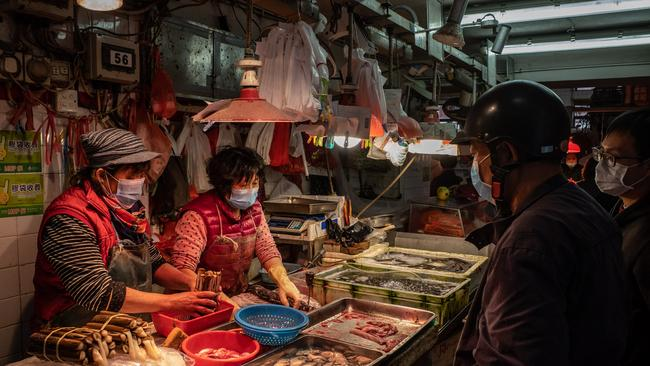 Residents wearing face mask purchase seafood at a wet market in Macau, China.
