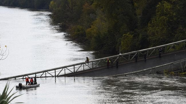 A 15-year-old girl was killed after a suspension bridge over a river collapsed on November 19, causing a car, a truck and possibly a third vehicle to plunge into the water, local authorities said. Picture: Eric Cabanis / AFP