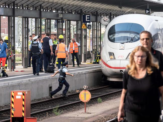 A police officer jumps onto the tracks. Picture: Frank Rumpenhorst/AFP