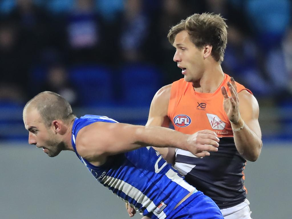 Ben Cunnington of the Kangaroos (left) chases the ball during the Round 13 AFL match between the North Melbourne Kangaroos and the GWS Giants at Blundstone Arena in Hobart, Sunday, June 16, 2019.  (AAP Image/Rob Blakers) NO ARCHIVING, EDITORIAL USE ONLY