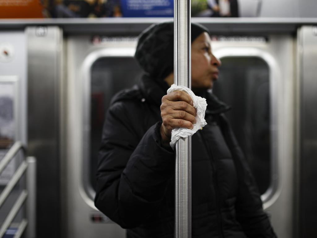 A subway customer uses a tissue to protect his hand while holding onto a pole while COVID-19 fears reducing the number of passengers in New York. Image: AP
