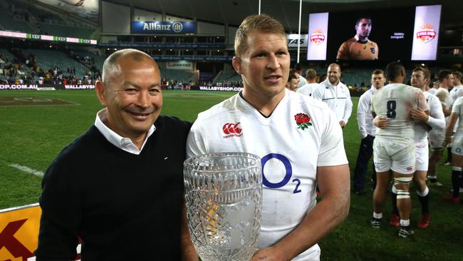 Dylan Hartley, the England captain, raises the Cook Cup with coach Eddie Jones.