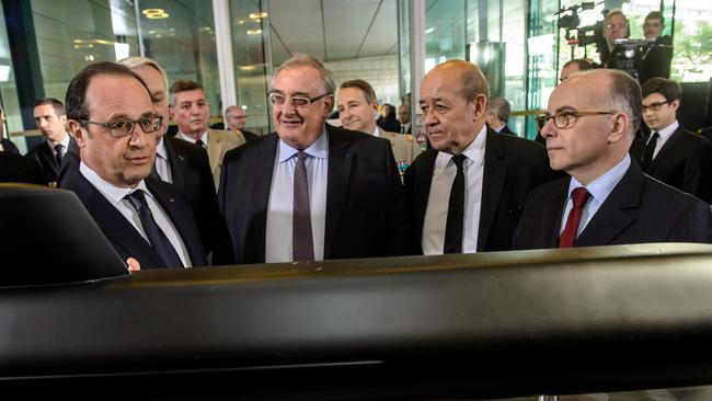 French President Francois Hollande, left, DCNS CEO, Herve Guillou, centre, Defense minister Jean Yves Le Drian, 2nd right, and Interior minister Bernard Cazeneuve, right, look at a model of a submarine displayed at the French industrial group DCNS headquarters in Paris. Australia's largest-ever defence contract has gone to a French shipbuilder to produce a new generation of submarines, thrilling officials in Paris. (Christophe Petit Tesson/Pool Photo via AP)