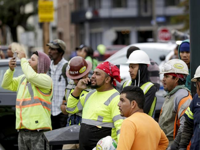 Construction workers look on after a large portion of a hotel under construction for several months suddenly came crashing down. Picture: Scott Threlkeld/The Advocate/AP