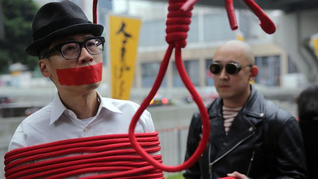 A protester is wrapped up with a rope made into a noose during a march calling for the release of missing booksellers from Hong Kong's Mighty Current publishing house known for books critical of Beijing. Picture: Isaac Lawrence