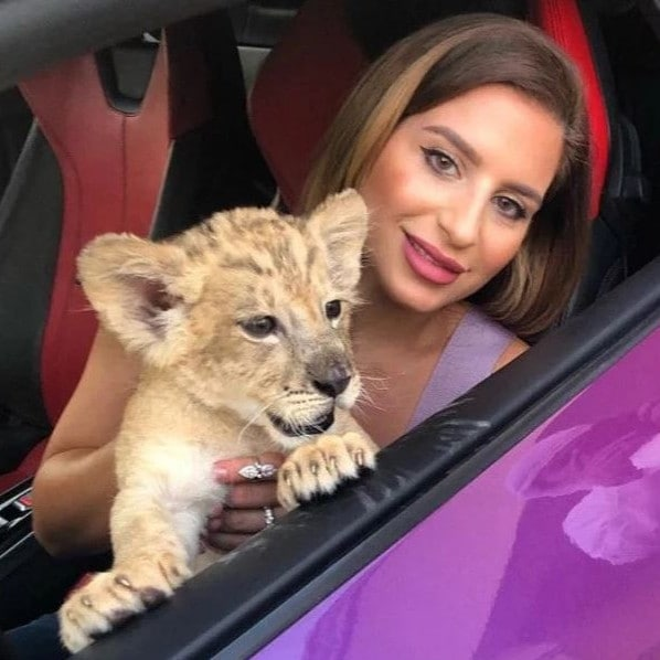 Natalia Itani, a Dubai influencer, poses with a lion cub in a purple Lamborghini Huracan. Picture: Instagram / naataliaitani