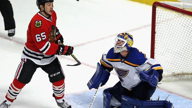 Andrew Shaw #65 of the Chicago Blackhawks watches as the puck sails over Brian Elliott #1 of the St. Louis Blues.