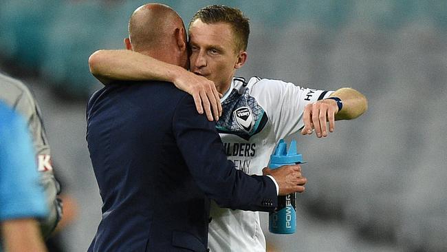 Besart Berisha of the Victory embraces coach Kevin Muscat.