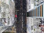 TOPSHOT - This overhead view shows thousands of protesters marching through the street as they take part in a new rally against a controversial extradition law proposal in Hong Kong on June 16, 2019. - Tens of thousands of people rallied in central Hong Kong on June 16 as public anger seethed following unprecedented clashes between protesters and police over an extradition law, despite a climbdown by the city's embattled leader. (Photo by STR / AFP)