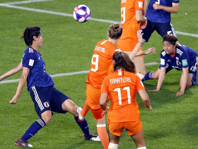 Japan's Saki Kumagai, left, reacts as the ball hits her from a shot by Netherlands' Vivianne Miedema.