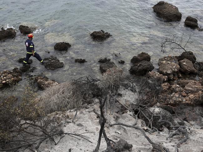 A member of a firefighter rescue team searches the burned coastline in Mati, east of Athens, where bushfires raged through seaside resorts. Picture: AP