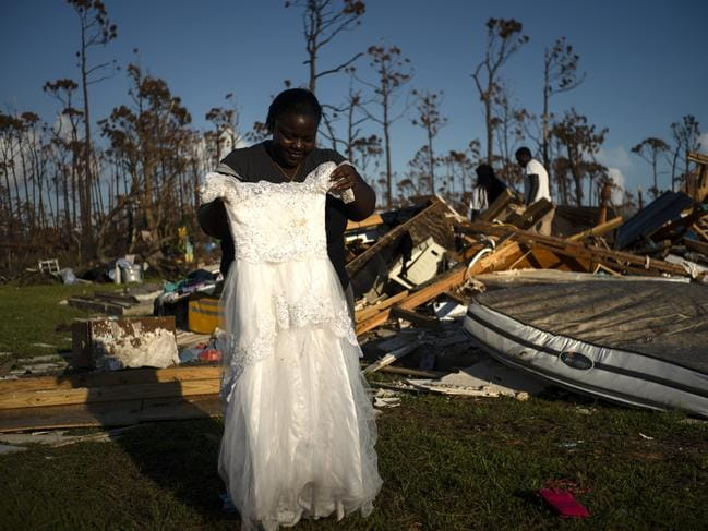 Synobia Reckley holds up the dress her niece wore as a flower girl at her wedding, as she goes through the rubble of her home destroyed by Hurricane Dorian. Picture: AP Photo/Ramon Espinosa