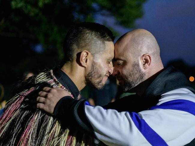 "A Muslim man and another local perform a traditional Maori ""hongi"" greeting in front of the Al Noor mosque. Picture: AFP"