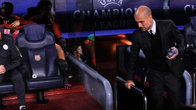 Manchester City's Spanish coach Pep Guardiola (R) returns to the Camp Nou dugout.
