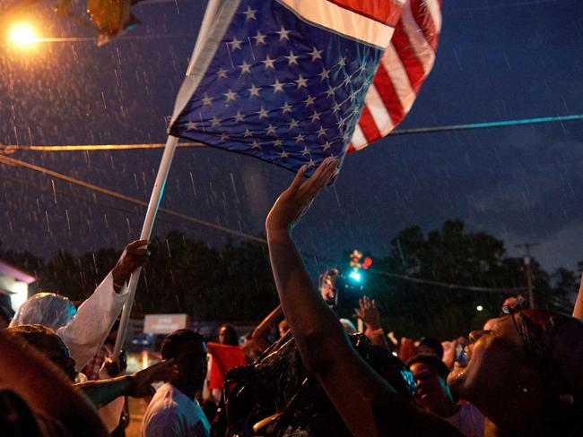TOPSHOTS Demonstrators participate in a protest march on West Florissant Avenue in Ferguson, Missouri on August 9, 2015. A day of peaceful remembrance marking the anniversary of 18-year-old black teen Michael Brown's killing by police in the US city of Ferguson came to a violent end on August 9 as gunfire left at least one protester injured. AFP PHOTO / MICHAEL B. THOMAS