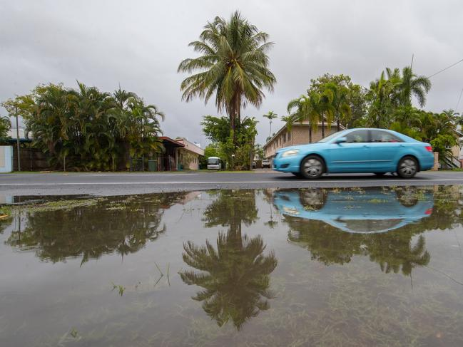 A vehicle passes water on the side of the road in Manunda, as Cyclone Owen dumps heavy rain in the region. Picture: AAP Image/Marc McCormack