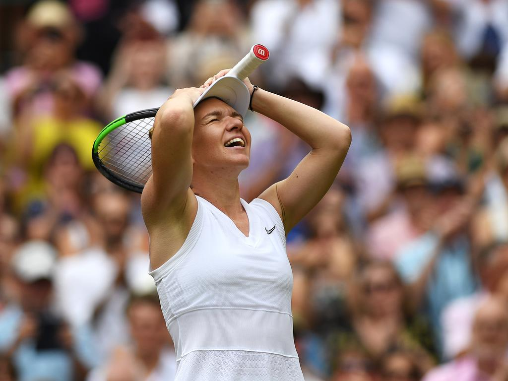 Simona Halep holds her head in her hands after winning championship point.