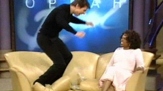 Tom Cruise jumps on the couch after proclaiming his love for actor Katie Holmes as host Oprah Winfrey looks on
