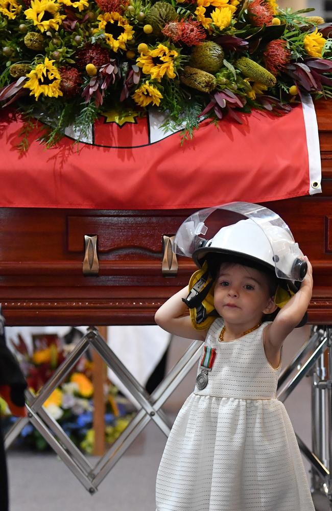 Charlotte O'Dwyer stands in front of her father's casket wearing his helmet after being presented with her father's service medal. Picture: Dean Lewins-Pool/Getty Images