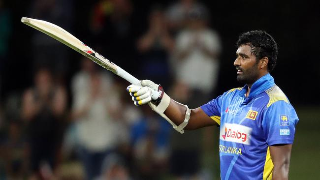 Perera raises his bat after scoring his maiden century. Photo: MICHAEL BRADLEY / AFP.