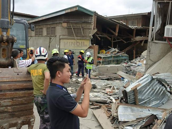 Residents and rescuers check damaged structures following an earthquake that struck Padada, Davao del Sur province, southern Philippines. Picture: AP Photo