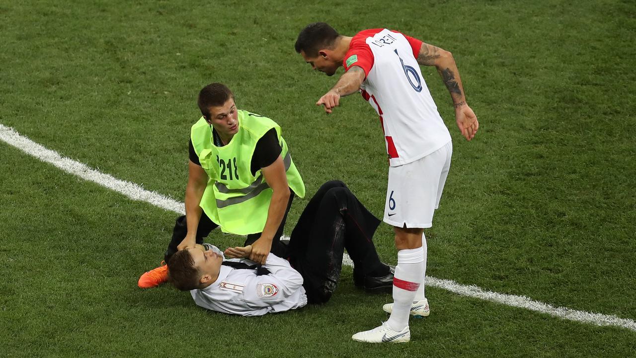 Dean Lovren of Croatia confronts a pitch invader.